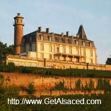 A nineteenth century chateau up on a hill surrounded by vineyards in Alsace