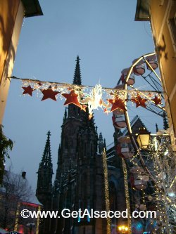 A snowy Christmas market  in Alsace with lights and a ferris wheel