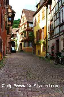 cobblestone lane surrounded by medieval Alsatian houses in Alsace