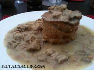meat and mushrooms in a creamy sauce served in a puff pastry cup