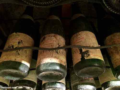 old white wine bottles aging in a wine cellar in alsace france
